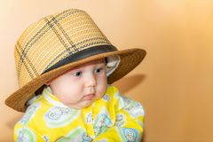 Portrait of a child, a little girl in a straw hat, in the studio on a beige background stock photos