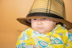 Portrait of a child, a little girl in a straw hat, in the studio on a beige background royalty free stock image