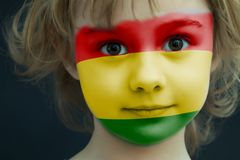 Child with a painted flag of Bolivia. Portrait of a child with a painted flag of Bolivia on her face, closeup Royalty Free Stock Photo