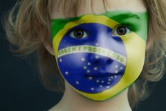 Child with a painted flag of Brazil. Portrait of a child with a painted flag of Brazil on her face, closeup Stock Photos
