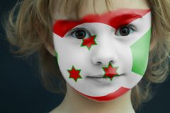 Child with a painted flag of Burundi. Portrait of a child with a painted flag of Burundi on her face, closeup Royalty Free Stock Images