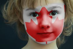 Child with a painted flag of Canada. Portrait of a child with a painted flag of Canada on her face, closeup Royalty Free Stock Image