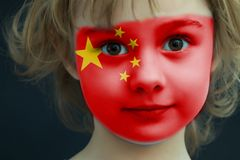 Child with a painted flag of China. Portrait of a child with a painted flag of China on her face, closeup Royalty Free Stock Photos