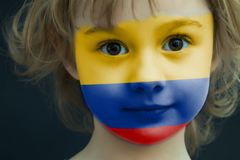 Child with a painted flag of Columbia. Portrait of a child with a painted flag of Columbia on her face, closeup Royalty Free Stock Images