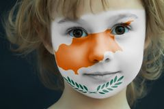Child with a painted flag of Cyprus. Portrait of a child with a painted flag of Cyprus on her face, closeup Royalty Free Stock Photo