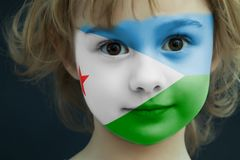 Child with a painted flag of Djibouti. Portrait of a child with a painted flag of Djibouti on her face, closeup Stock Photography