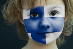 Child with a painted flag of Finland. Portrait of a child with a painted flag of Finland on her face, closeup Stock Photos