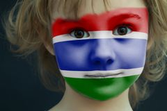 Child with a painted flag of Gambia. Portrait of a child with a painted flag of Gambia on her face, closeup Royalty Free Stock Photography