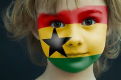 Child with a painted flag of Ghana. Portrait of a child with a painted flag of Ghana on her face, closeup Royalty Free Stock Image