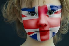 Child with a painted flag of the Great Britain. Portrait of a child with a painted flag of the Great Britain on her face, closeup Royalty Free Stock Image