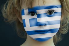 Child with a painted flag of Greece. Portrait of a child with a painted flag of Greece on her face, closeup Stock Photography