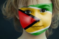 Child with a painted flag of Guyana. Portrait of a child with a painted flag of Guyana on her face, closeup Stock Photo