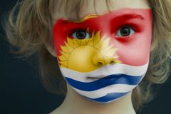 Child with a painted flag of Kiribati. Portrait of a child with a painted flag of Kiribati on her face, closeup Royalty Free Stock Image