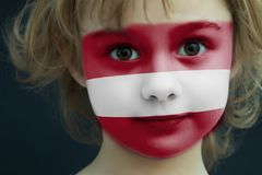 Child with a painted flag of Latvia. Portrait of a child with a painted flag of Latvia on her face, closeup Royalty Free Stock Images