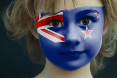 Child with a painted flag of New Zealand. Portrait of a child with a painted flag of New Zealand on her face, closeup stock photos