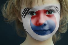Child with a painted flag of south korea. Portrait of a child with a painted flag of south korea on her face, closeup stock photos