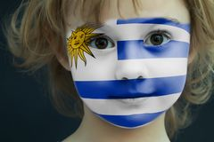 Portrait of a child with a painted Uruguayan flag. On her face, closeup Stock Photos
