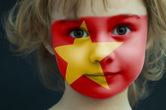 Portrait of a child with a painted Vietnamese flag. On her face, closeup Stock Images