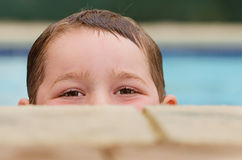 Portrait of child peeking over edge of pool. While swimming Royalty Free Stock Photography