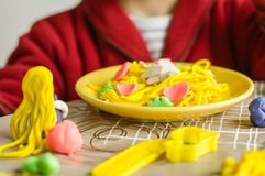 Portrait of child with plasticine spaghetti dish. Portrait of cute child posing with his original spaghetti dish, made in colorful plasticine royalty free stock photography