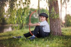 Portrait of child playing with bow and arrows, archery shoots a Royalty Free Stock Photos