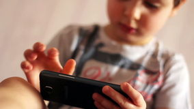 Portrait of a child playing with a smartphone stock video