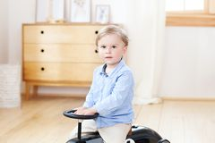Portrait child riding toy vintage car. Funny kid playing at home. Summer vacation and travel concept. Active little boy driving a. Car pedal in the nursery stock image