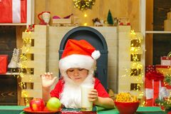 Portrait of child Santa Claus Drinking milk from glass and holding cookies. Santa Claus takes a cookie on Christmas Eve