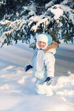 Portrait of Child shakes off snow trees Royalty Free Stock Photo