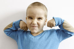 Portrait of a child showing his strength. Casual boy showing his muscles and power Stock Photo