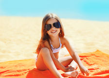 Portrait of child sitting on the beach in sunny day Royalty Free Stock Images