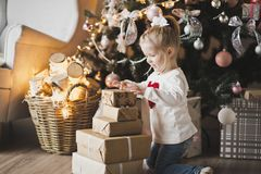 A little girl sitting under the Christmas tree with gifts 7249. Stock Image