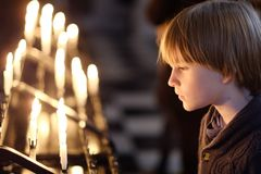 Portrait of a child standing by the burning candles. At St. Paul`s Cathedral in London, UK stock images
