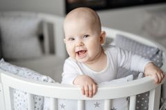 Portrait of a child staying in his baby cot and smiling. stock photo