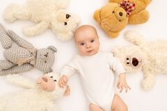 Portrait of a child on a white background with plush bear toys. Baby 6 months among toys. Space for text