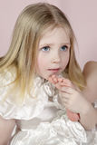 Portrait of the child in a white dress with a foot near a mouth Royalty Free Stock Photos