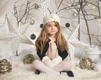 Portrait of Child in White Winter Background. A little girl is sitting in a white winter wonderland setup with trees, hanging stars and Christmas lights in the royalty free stock image