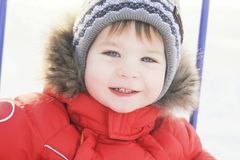 Portrait of a child in winter clothes, a walk through a winter park, Royalty Free Stock Image
