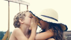 Portrait of children on the beach in summer. Little girl in a hat whispering with her brother and smiling. They are stock image