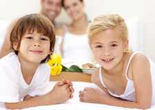 Portrait of children in bed with their parents Stock Images
