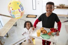 Portrait Of Children Bringing Parents Breakfast In Bed On Tray With Balloon To Celebrate Birthday royalty free stock photos