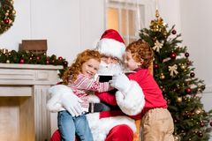 Santa claus and children with digital devices. Portrait of children with digital devices hugging santa claus in rolling chair Stock Photography