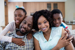 Portrait of children embracing their parents in living room Stock Photography