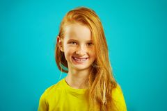 Portrait of children girl with cute smile, has red hair and beautiful freckles, dressed in bright t-shirt, child shot on royalty free stock photo