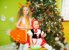 Portrait of children girls in a suit squirrels around a Christmas tree decorated. Kids on holiday new year Stock Photography