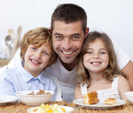 Portrait of children having breakfast with their f Stock Photos
