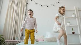 Portrait of children jumping on a bed, little boy and girl brother and sister have fun and laughing