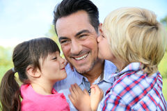 Portrait of children kissing their father. Portrait of kids giving a kiss to their daddy Stock Photos