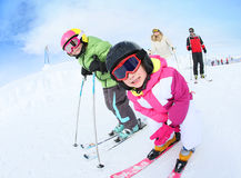 Portrait of children learning skiing with family Royalty Free Stock Images