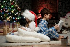Portrait of children with letters under the Christmas tree by the fireplace. Two children reading letters from Santa Claus on the Christmas tree pillows Royalty Free Stock Images